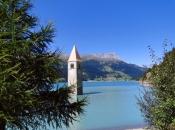 Der herausragende Kirchturm von Graun am Reschensee im Vinschgau als Wahrzeichen der Ferienregion Reschen
